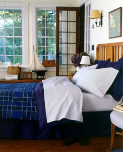 Bed with blue blanket in bedroom