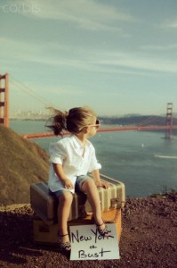 Little girl sitting on suitcase looking out onto Golden Gate Bridge